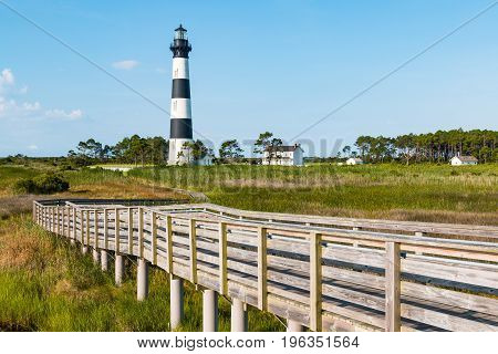 Historic Bodie Island lighthouse, surrounding buildings and wooden walkway to observation point.  It is located south of Nags Head on the Outer Banks in North Carolina.