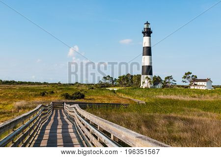 Wooden ramp over marshland leading to an observation point, with the the Bodie Island lighthouse in the background, on the Outer Banks of North Carolina near Nags Head.