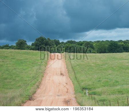 A lonely dirt road and an ominous dark sky gives the sense of mystery as to what may await just over the hillside.
