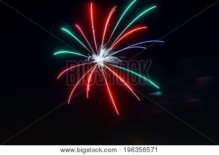 Sparkling red green yellow celebration fireworks over starry sky. Independence Day 4th of July New Year holidays salute background.
