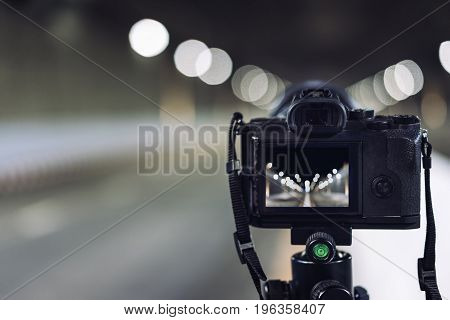 camera on tripod on subway tunnel with light bokeh