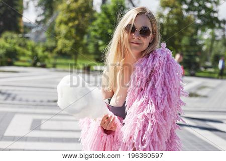 Caucasian blond student girl with cotton candy in hand wearing pink funky coat and round sunglasses resting in city park after lectures at university. Happy young woman with cheerful dreamy smile.