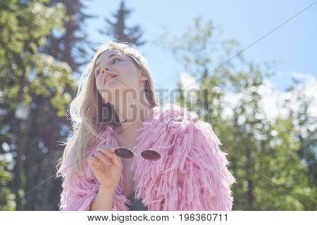 Good-looking blond Caucasian female wearing pink funky coat standing outdoors in city park with white walls holding sunglasses waiting for romantic date dreaming about love with sincere smile