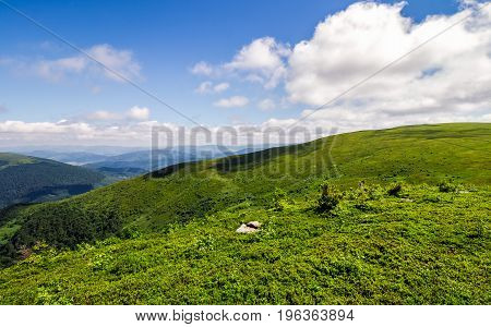 Grassy Meadow On Hillside Of Mountain Range On Fine Summer Day