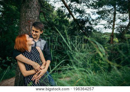 Love couple kissing under a tree, readhead girlfriend