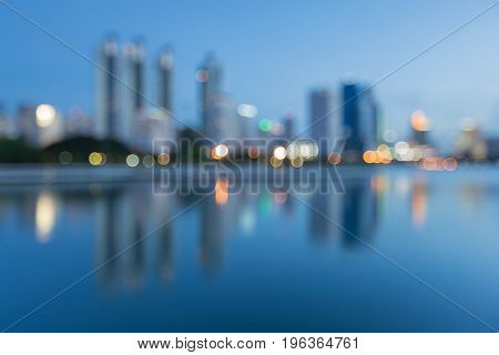 Blurred bokeh city light at twilight with water reflection abstract background