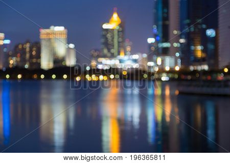 Abstract blurred light night view with water reflection office building twilight background