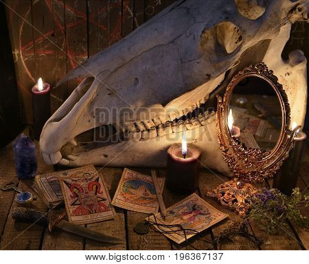 The Tarot cards, magic mirror and horse skull against the planks with pentagram. Mystic still life with scary occult objects, horror Halloween concept, fortune telling or divination rite