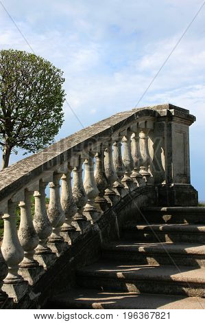 Stone staircase with beautiful marble railing against the blue sky