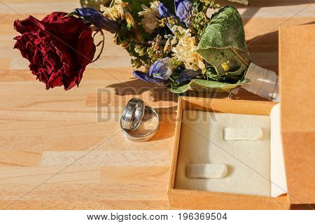 Wedding Rings With Dry Rose And Flower And Box On Wooden Background