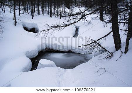 frozen creek during winter in alpe devero