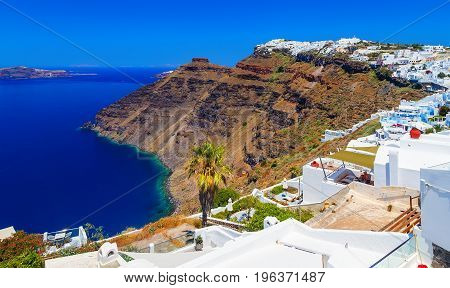 Hotels of Fira town on the slopes of volcanic mountain overlooking the sea and Caldera of Santorini, Greece.