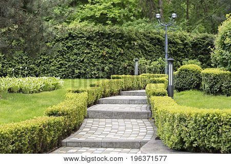 A paved stepped path in a beautiful park passes through a green lawn with decorative flowers framed on both sides by sheared bushes and lanterns for lighting