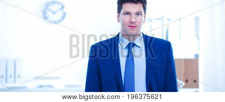 Successful business young man standing in office