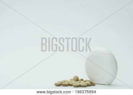 Tablets and pill box on white background