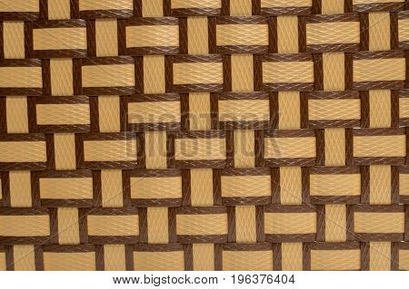 Brown and yellow plastic weave pattern texture background, handmade