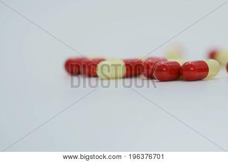 Red, yellow antibiotic capsule pills on white background