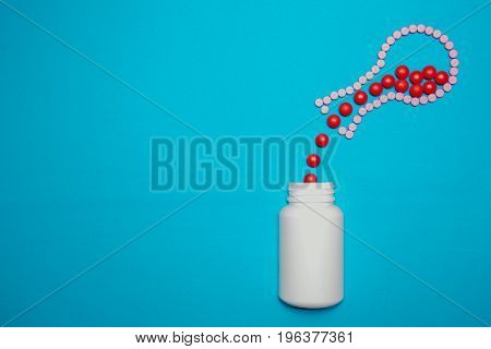 Red pills spilling out of round bottom flask that made of pills into the white bottle on blue background
