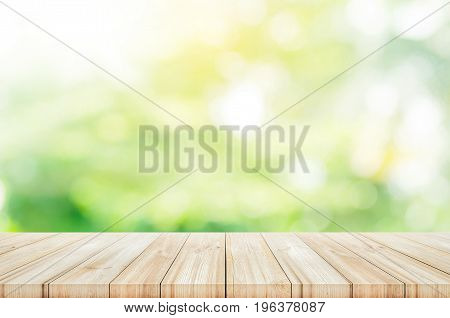 Empty wooden table top with blurred green garden background. can be used product display.
