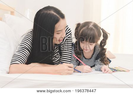 Happy Family In The Bedroom,yong Mother Teaching Her Daughter Child To Studying At Home.photo Series