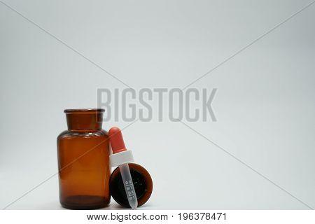 Amber glass bottle whit plastic dropper on white background
