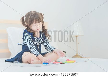 Cute Asian Little Girl Enjoy Playing With Toy Set While Sitting On Bed In Kid's Bedroom At Home.
