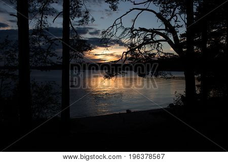 Sunset in the sky with clouds on a lake with silhouettes of trees in summer