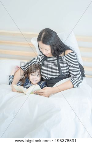 Happy Loving Family Young Asian Mother Reading Funny Book With Her Cute Daughter In  Bedroom.photo D