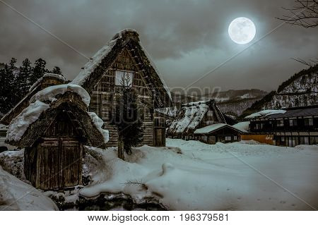 Snow Covered The Ground In Winter. Town With Night Sky And Full Moon. Vintage Tone.