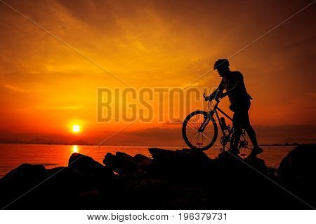 Silhouette of bicyclist enjoying the view at seaside on colorful sunset orange sky background. Reflection of sun in water. Active outdoors lifestyle for healthy concept.
