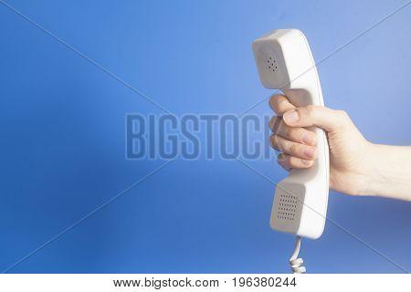 Hand Holding White Telephone Tube On Blue Background.