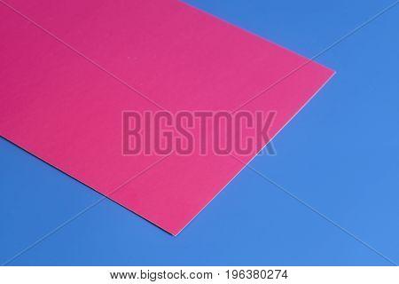 Purple paper sheet on blue background .