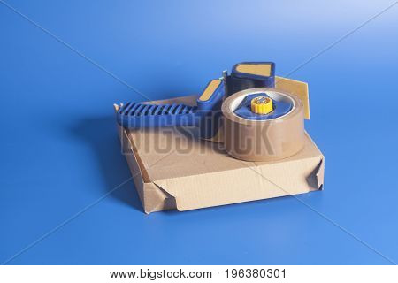 Dispenser With Cardboard Box On Blue Background