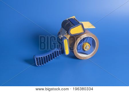 Dispenser industrial scotch-tape on blue background .