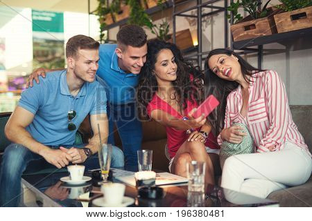 Group of young people meeting in a cafe make selfie photo.