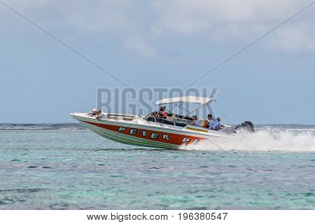 Blue Bay Mauritius - December 27 2015: Luxury private speed boat sails with tourists on the Blue Bay Beach one of the finest beaches in Mauritius and the site of many tourism facilities.