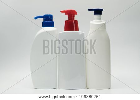 Three white bottles with red and blue pump