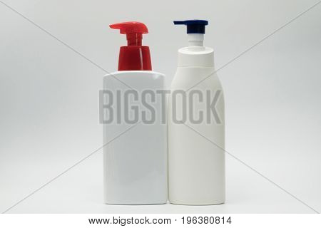 Two bottles of skincare with pump on white background