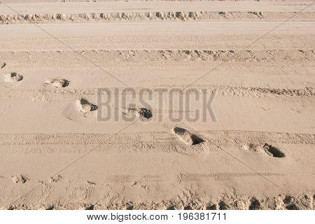 Traces of people in the sand of a beach. Pure sand on the beach as a background texture. Top view. Selective focus.