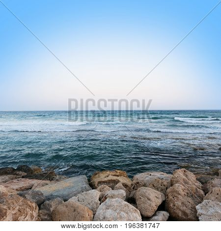 Soft Wave Of Blue Ocean On Sandy Beach background. Selective focus. Seascape at sunset