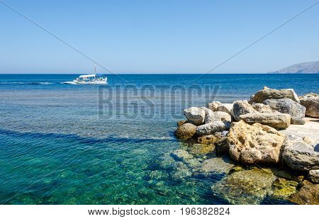 Smal fishing boat floating on turquoise calm waters of Skiros island Greece