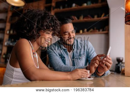 Young happy couple sitting at table in cafe and looking at mobile phone and smiling. African woman and caucasian man in coffee shop using smart phone.