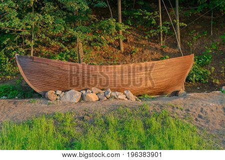 An old longboat stands on the shore at the foot of a wooded hill
