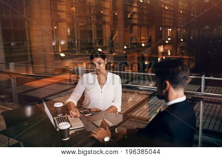 Businesswoman sitting at cafe table with man discussing business. Business people waiting at airport lounge with laptop.