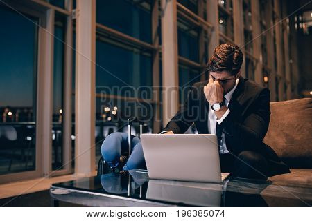 Tired Businessman Waiting For Delayed Flight In Airport Lounge