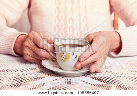 An elderly woman drinks tea at home. Senior woman holding cup of tea in their hands at table close-up