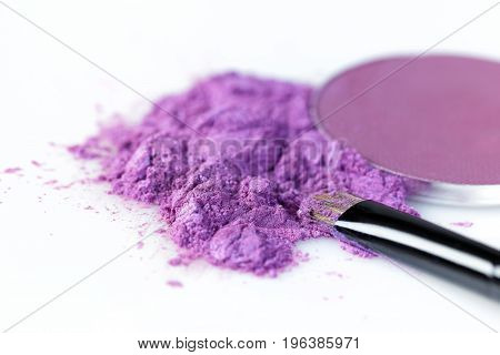 crushed purple eye shadow and makeup brush isolated on the white background