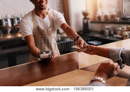 Cropped shot of customer giving credit card to male barista at cafe checkout counter. Customer paying through credit card at coffee shop.