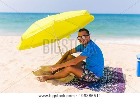 Lazing Man In Sun  Under Solar Umbrella On Towel Enjoy The Lazy Time On The Beach