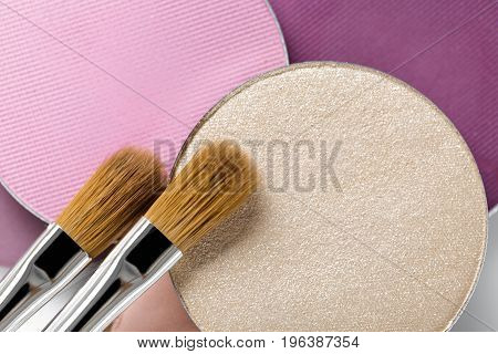 Palette of pink and beige eye shadow and the makeup brush, top view